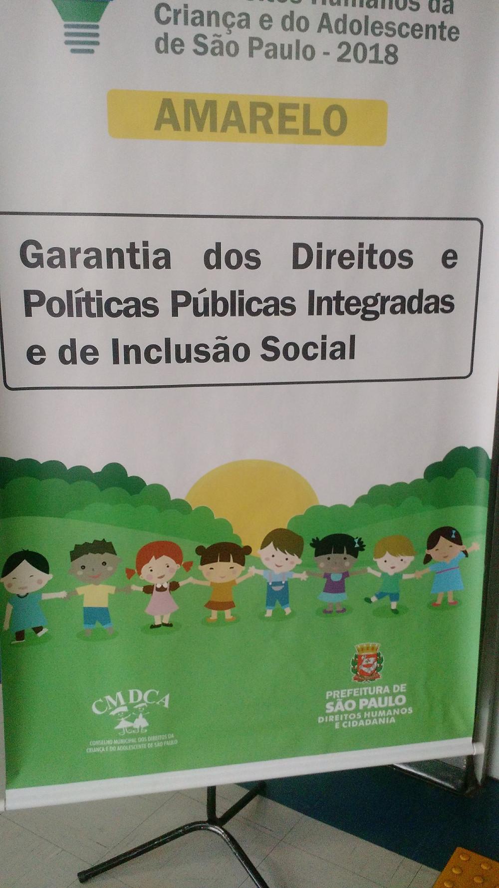 Placa de identificação na porta de uma sala de aula com os dizeres Eixo Amarelo: Garantia dos Direitos e Políticas Públicas Integradas e de Inclusão Social