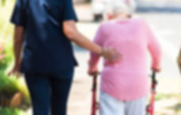 carer walking with elderly woman