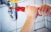 plumber repairing pipe for senior