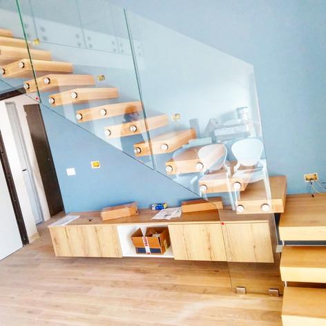 gradini in massello di faggio fissati singolarmente a parete, barriera in vetro con fissaggi a punto