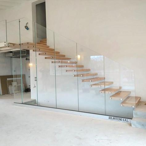 gradini in massello di faggio fissati singolarmente a parete, barriera in vetro con scarico a terra