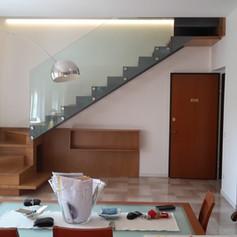 scala a giorno in legno di faggio, con struttura laterale e alzate chiuse, barriera in vetro con fissaggi a punto