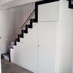 scala a giorno con doppia struttura laterale nera con barriera in acciaio inoz verticale e armadiatura bianca laccata