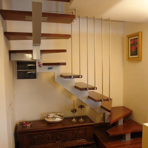 scala a giorno con struttura centrale a triangolo chiuso, gradini in massello di faggio e barriera con tondi in acciaio inox verticali.