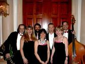 Swizzle Sisters gig at fancy hotel, circa 2009. L-R: Greg Loeb, guitar, vocals; Donna Greene, vocals; Bill Rangel, drums; Margie Nelson, vocals; JED, piano; Anne Shaw, vocals; Steve Carmel, bass