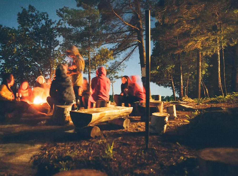Family sitting around a bonfire at Nitschke's Northern Resort