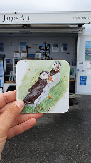 Two Green Puffins standing in the green grass on a rock table coaster