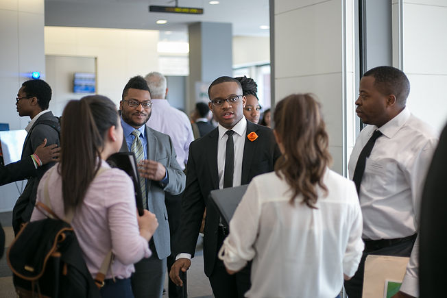 Group of young Black people in professional attire. They're talking and smiling inside an office building.