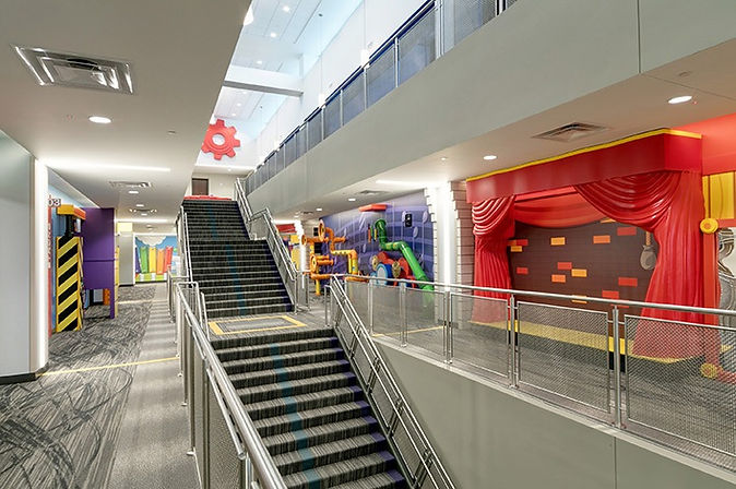 Interior of the Potter's House facility in Dallas, TX. There are stairs leading up multiple levels, carpeted floors, and colorful walls.