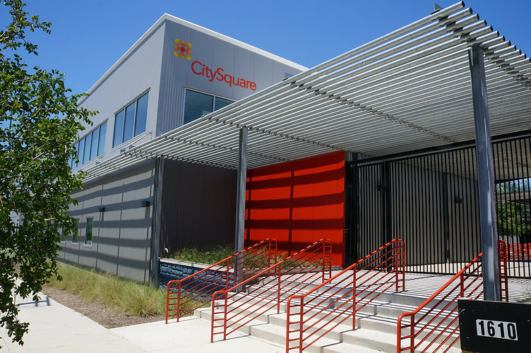 Close-up exterior of CitySquare Dallas in the day. The building features grey metal walls with a red accent wall at the entrance.