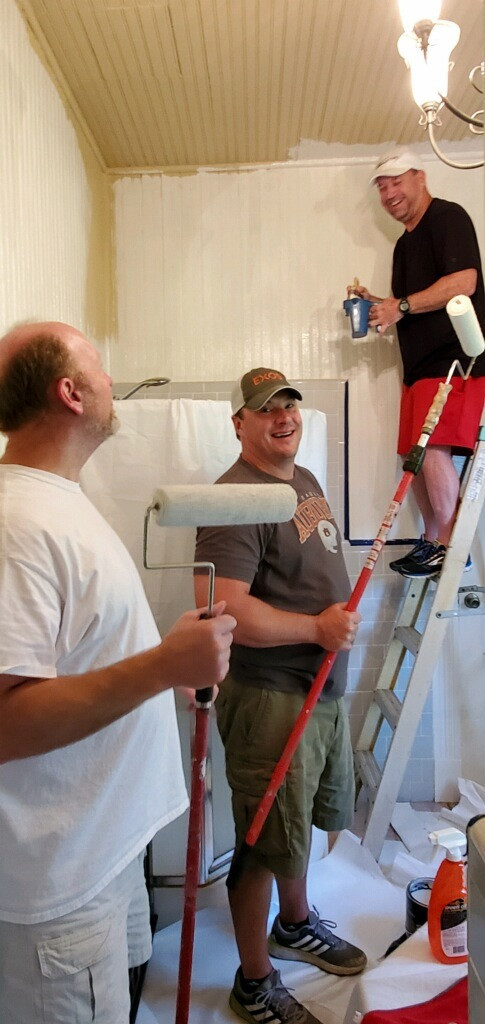 Three men painting a room.