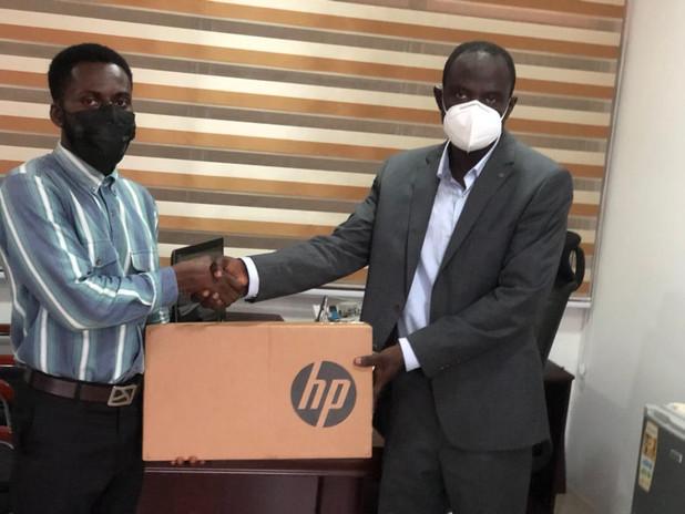 Dr. Emmanuel Quansah, JEQ Foundation Rep. presenting a new laptop to Samuel