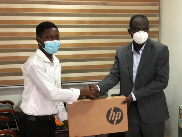 Dr. Emmanuel Quansah, JEQ Foundation's Ashanti rep. presenting a new laptop to Nii.