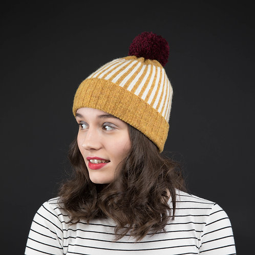 Mustard yellow hat with white stripes and bordeaux pom pom