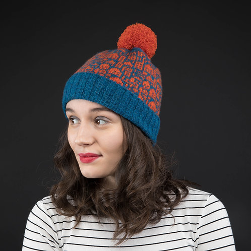 Orange and blue hat with little city pattern and orange pom pom
