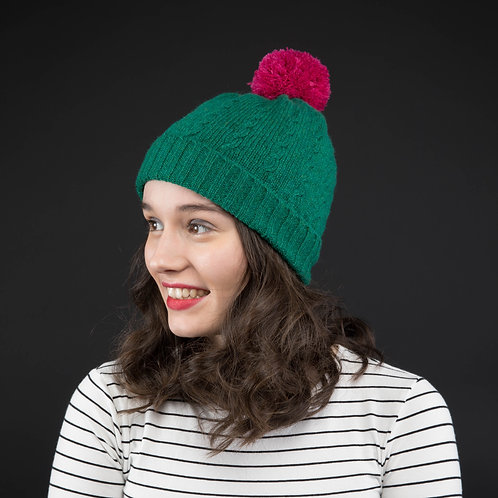Green cable knit hat with pink pom pom