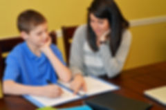 Tutor helping a young student with his s