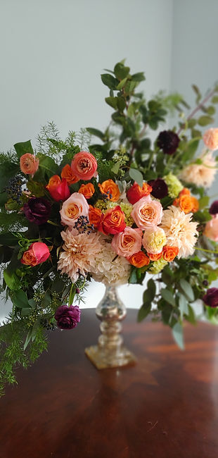 A bright and bold contemporary style floral arrangement, featuring coral, orange, and pink roses, dark purple ranunculus, and creamy dahlias surrounded by eucalyptus.