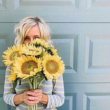 Overland Park local florist Jennifer Hall smiles and holds a cheery bouquet of yellow sunflowers.