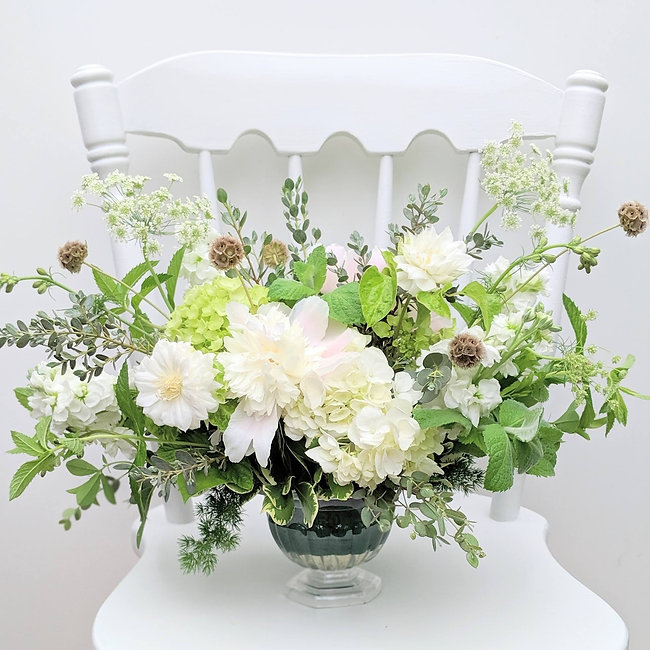 An elegant wedding floral arrangement of white hydrangea, stock, queen anne's lace, and other light and airy bridal flowers.