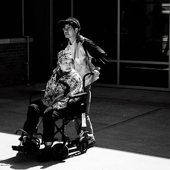 A man pushing a mature lady in a wheelchair.