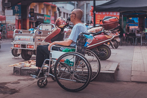 An elderly man sitting in his wheelchair on a busy street.