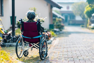 An elderly lady sitting in a wheelhair looking downa cobbled street.