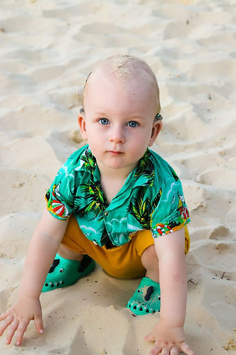 A photograph of a very young boy sat on sand wearing hearing aids.