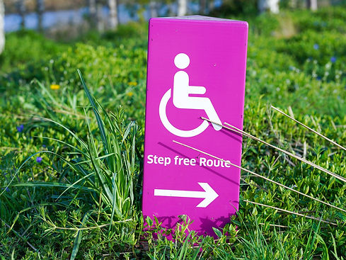 Image of a pink sign set into grass. The sign shows the disability wheelchair symbol and the words Step free Route and an arrow on it.