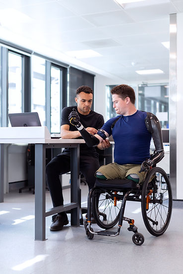An image of Alex Lewis who is a qualdruple amputee sat in his wheelchair while an engineer fits a prosthetic arm.