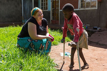 An image of a young girl from Southern Africa walking with crutches while an adult smiles at her.