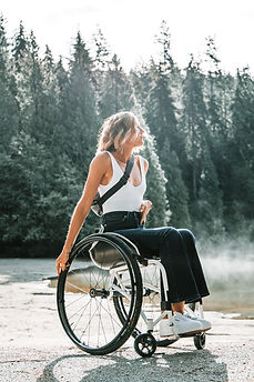 A young woman sitting in her manual wheelchair outside with pine trees behind her.