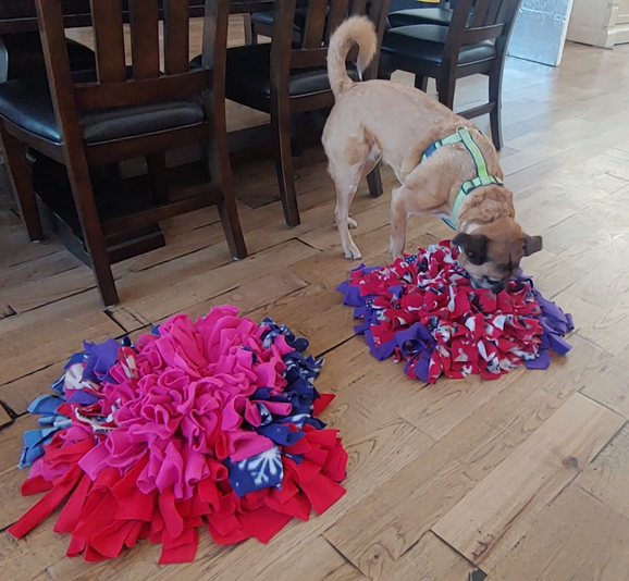 Dog using 2 DIY snuffle mats made of scrap fleece for food puzzle