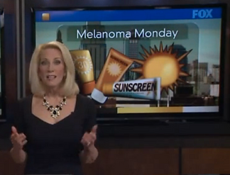 Local TV news anchor in front of a screen saying Melanoma Monday