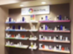 "12 small shelves holding a large variety of skin care products with a sign saying ""Skin Type Solutions"" above it"