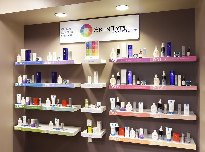 """12 small shelves holding a large variety of skin care products with a sign saying """"Skin Type Solutions"""" above it"""