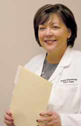 Physician Assistant Tammy Grosserode in a white lab coat and holding a manila folder