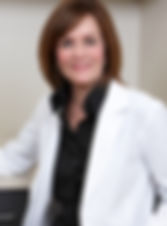 Nurse practitioner Barbara Delcore wearing a white lab coat in the office