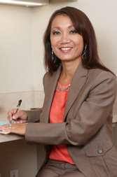 Nurse practitioner Mary Zahau-Loehner wearing a brown pantsuit and writing