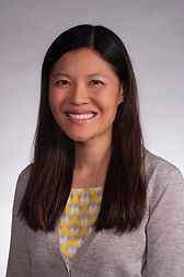 Professional headshot of Dr. Wenfei Xie in a gray cardigan in front of a subtle gray background