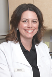 Aesthetician Ashley Roth wearing a white lab coat and smiling