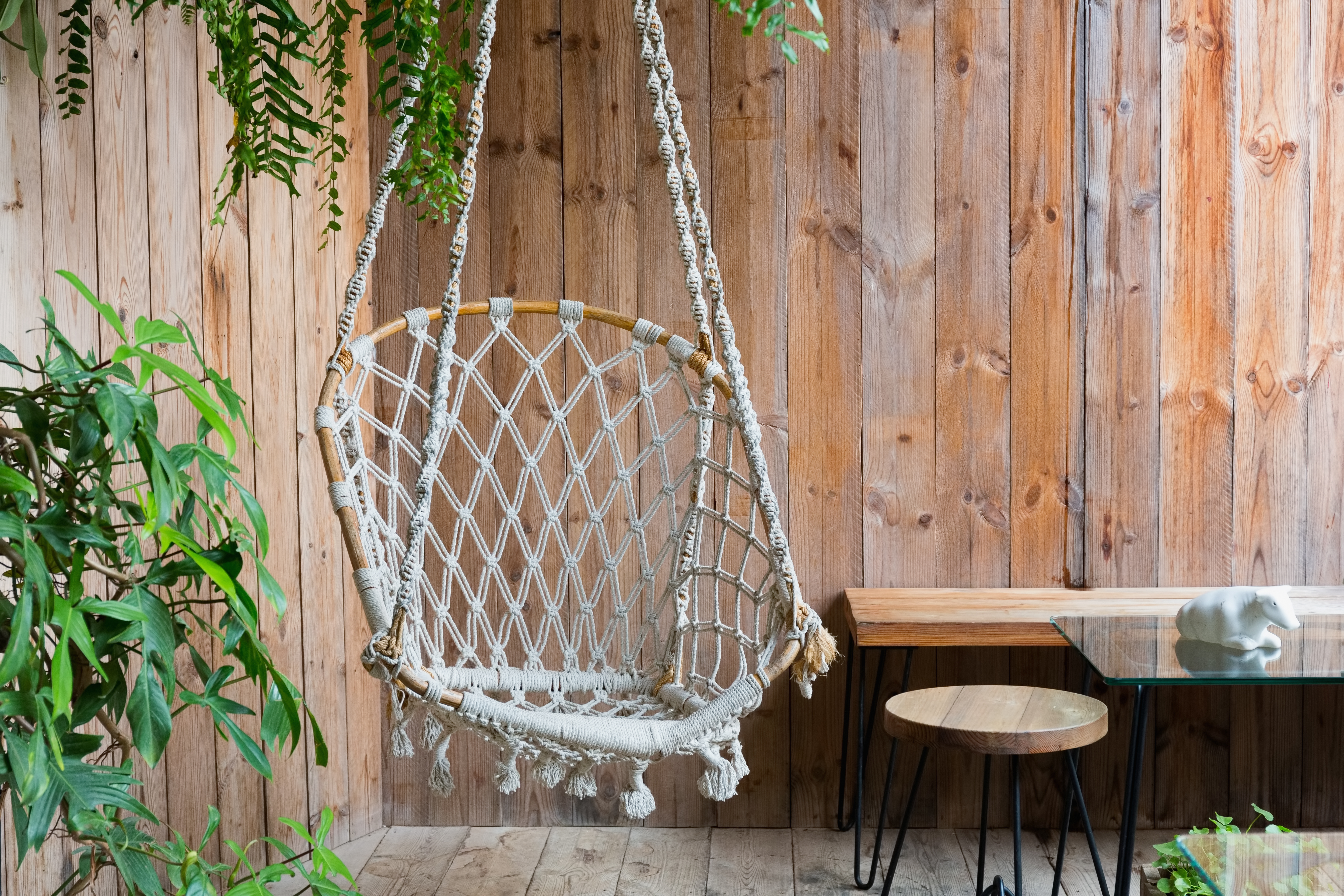 Hanging rope chair in a wooden patio wit
