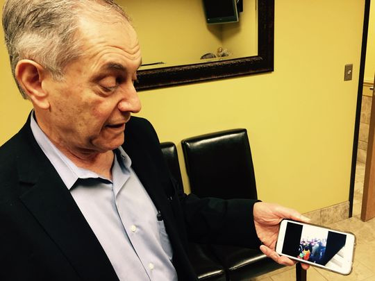 In his office in Royal Oak, Dr. Yahya Basha looks at a video of relatives who are Syrian refugees on a boat from Greece to Macedonia. (Photo: Niraj Warikoo, Detroit Free Press)