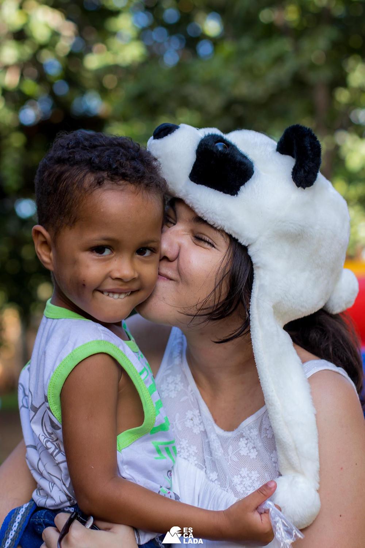 Carol Fraga beijando dando carinho a uma criança na creche