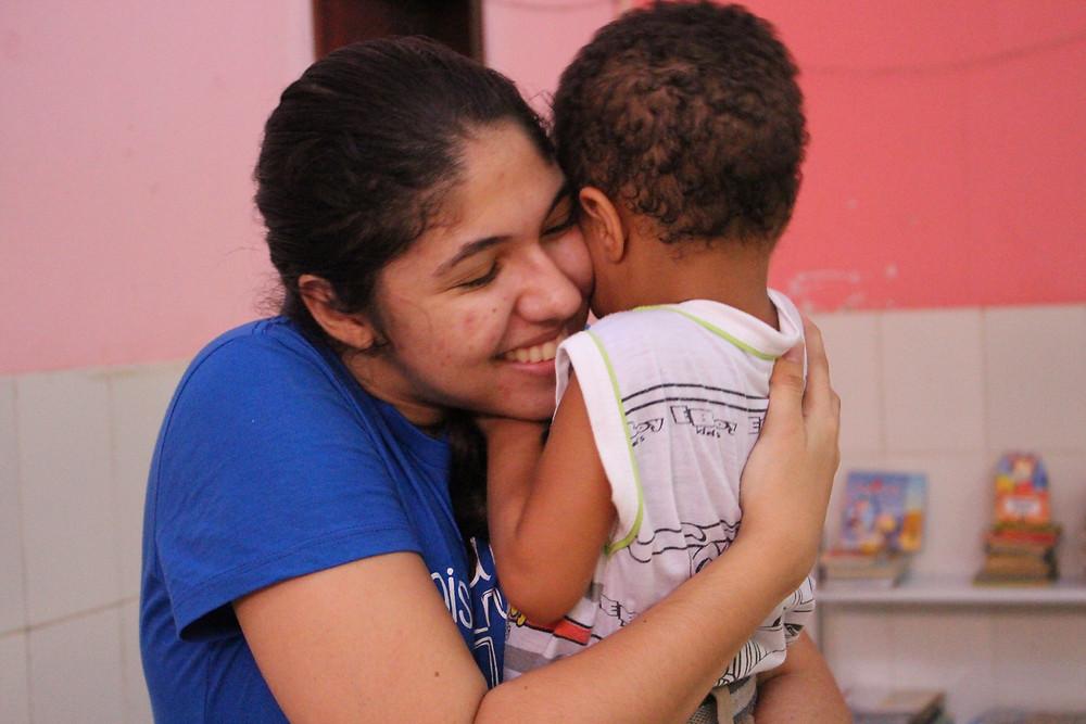 Carol Fraga abraçando criança na creche