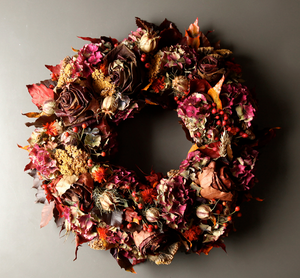 An autumn wreath made out of dried flowers and foliage with Hydrangea, Achillea, Rose hips, Berries, Maple-leaf roses