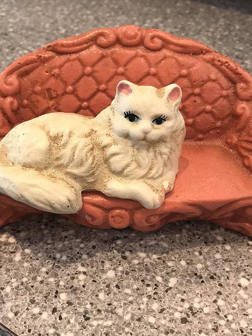 cast iron piggy bank, pink sofa cat, white persian, comfy decor