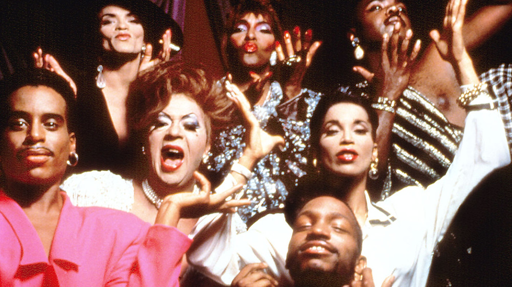 """This photo stems from a documentary entitled """"Paris is Burning"""" which revolves around the ballroom scene. It focuses on the specific experiences of Black and Brown men as well as transgender women. The purpose of the documentary was to provide information on the club and ballroom scene and to open the eyes of straight audience members to depict the struggles faced by members of the LGBTQ community. (Image Source: Academy Entertainment)"""