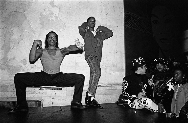 "Willi Ninja and friends voguing at ""Mars"", a nightclub in New York City, in 1988. Ninja founded the House of Ninja, a safe space for struggling queer youth (Image Source: Catherine McGann)"