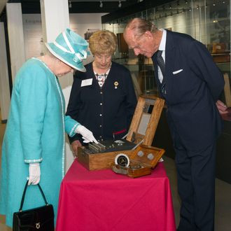 """Her Royal Majesty Queen Elizabeth II and her husband, His Royal Highness Prince Philip observing an enigma machine at Bletchley Park in 2011. The Queen later went on to issue Alan Turing a royal pardon for his so-called """"crimes."""" (Image Credit: Arthur Edwards/Associated Press)"""